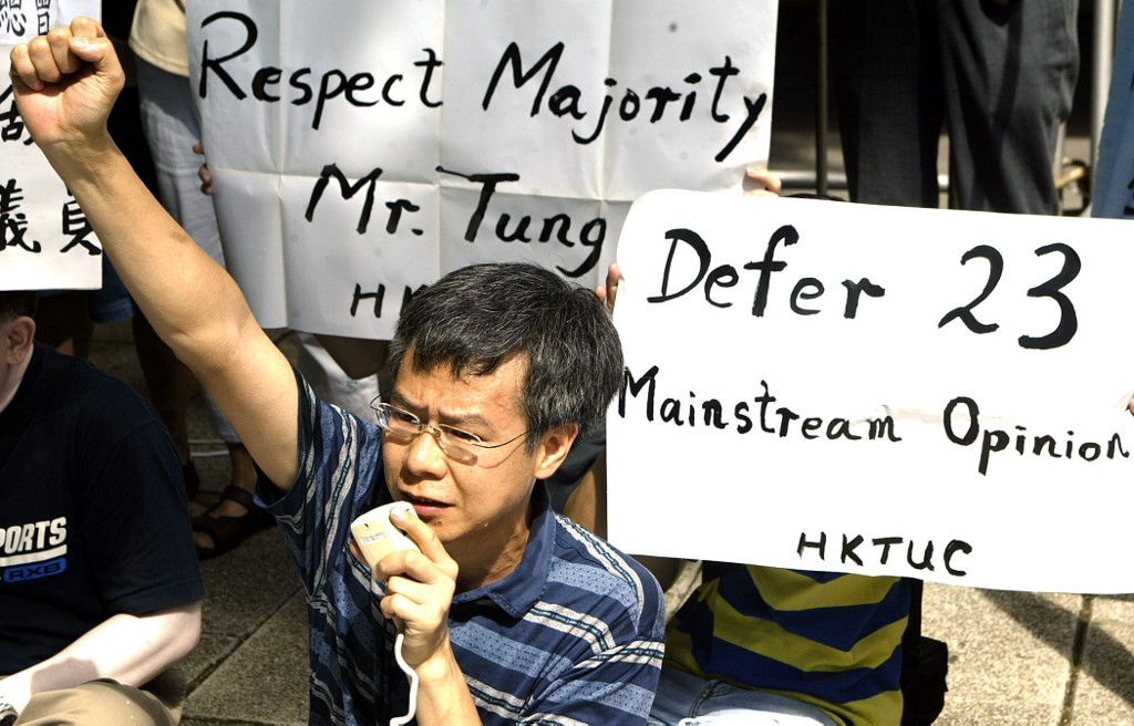 REJECT. A Member of the Hong Kong Trade Union Council holds placards and denounces the government's proposed national security bill in 2003. File photo by Peter Parks/AFP
