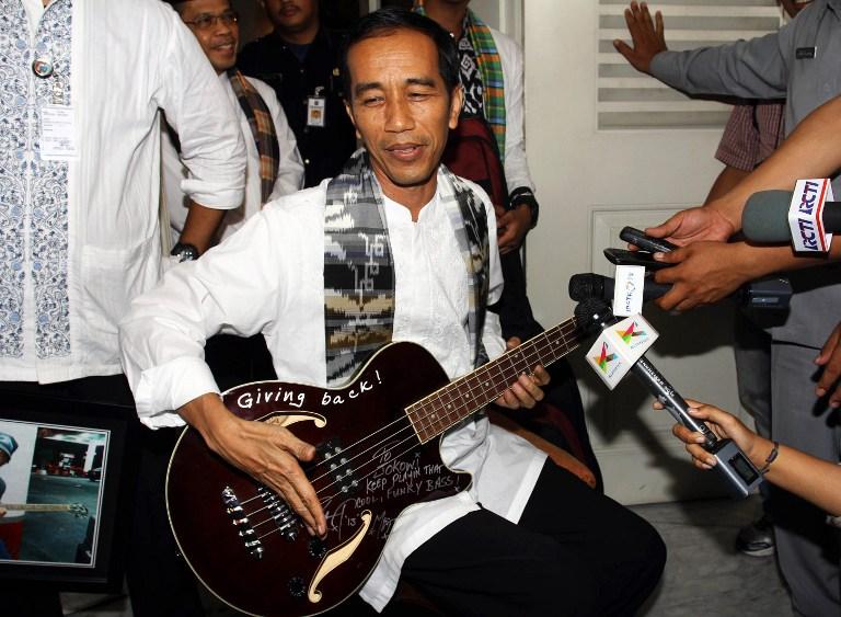 Jokowi memainkan bass yang diberikan oleh bassist band Metallica. Foto oleh AFP