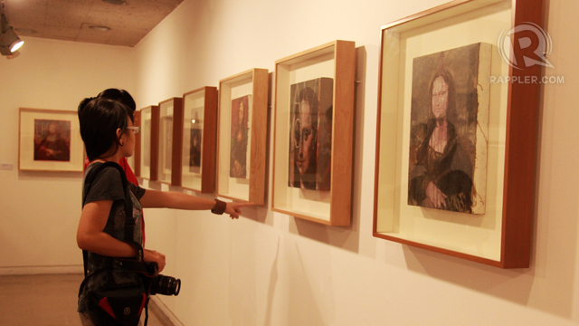 FREE EXHIBIT. Visitors look at some wall-bound pieces in the free exhibit 'The Mona Lisa Project'