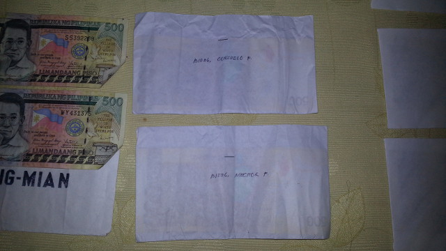LABELLED. A barangay official surrenders envelopes containing P500 bills and labelled with names of voters to the former governor of Southern Leyte. Photo courtesy of Eva Tomol