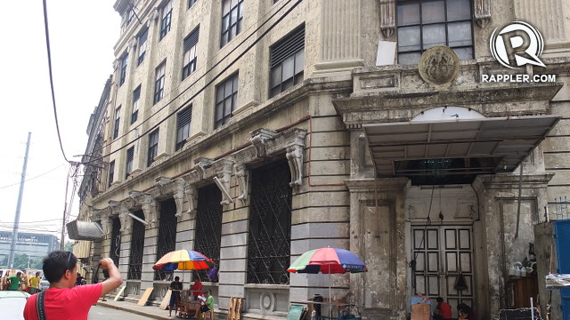 WASTED HERITAGE. A tourist takes a photo of a decaying building in Escolta, once Manila's thriving financial district. Photo by Pia Ranada