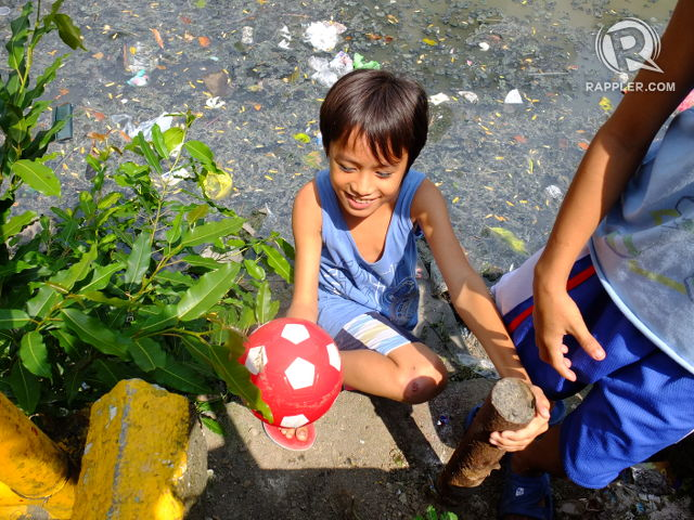 PRIZES FROM THE ESTERO. A boy picks out a ball he found floating in the creek