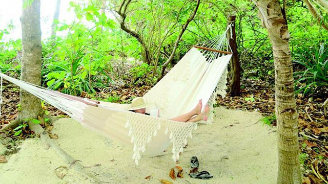 PRIVATE PARADISE. The author while in Amanpulo, reading a book in a hammock between the casita and a private beachfront. Photo by Lisa Cruz
