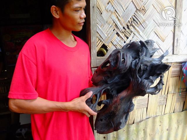 DRIFTWOOD ART. Joselito, a Dumagat, holds a piece of driftwood art