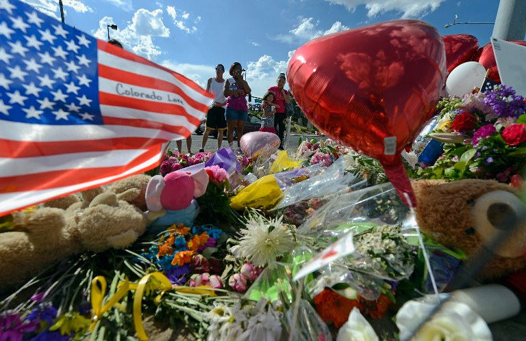 Tiffany Garcia (R) and her six-year-old daughter, Angelina Garcia, cry as they look at a makeshift memorial across the street from the Century 16 movie theater the day after a gunman killed 12 people and injured 59 during an early morning screening of 'The Dark Knight Rises,' July 21, 2012 in Aurora, Colorado. Police in Aurora, a suburb of Denver, say they have the suspect James Holmes, 24, in custody. Kevork Djansezian/Getty Images/AFP