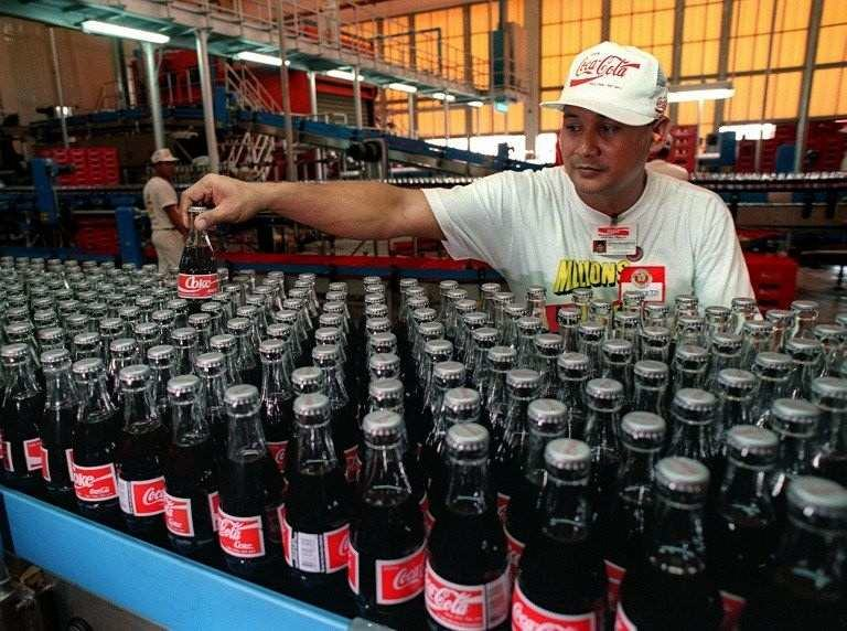 BOTTLING STAYS. The concentrate plant is transferred to Singapore but bottling and distribution stays. File photo by AFP