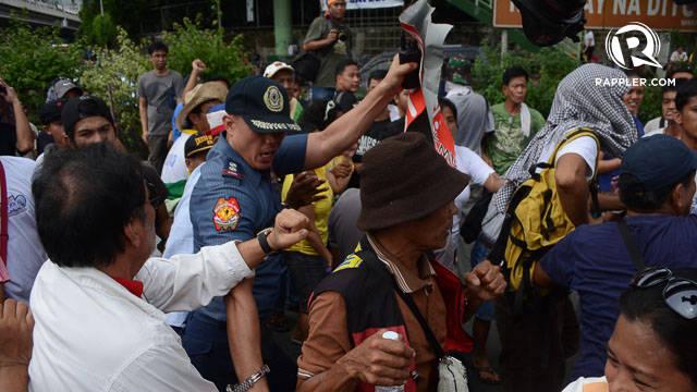 NO PLACARDS. A police officer rips apart one protester's placard at the EDSA Tayo u0022prayer vigil.u0022 Photo by Mark Demayo