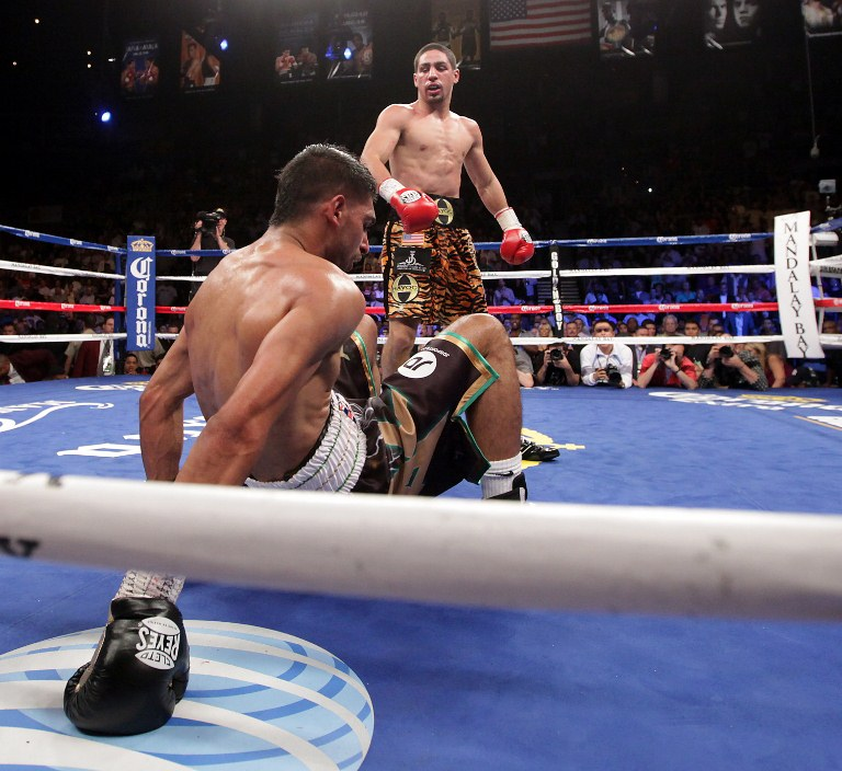 HUGE UPSET. Danny Garcia (top) from Philadelphia, Pennsylvania, stands over Amir Khan, from Bolton, England after knocking him down to the canvas in the fourth round on July 14, 2012 at the Mandalay Bay Events Center in Las Vegas, Nevada. Photo from AFP.