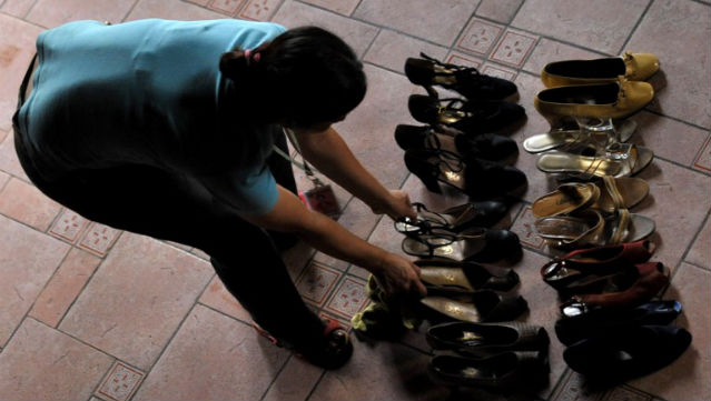 DAMAGED. Amid the deluge of Ondoy in 2009, a staffer at the Marikina Shoe Museum salvages Imeldau2019s shoes. Photo: Jay Directo/AFP