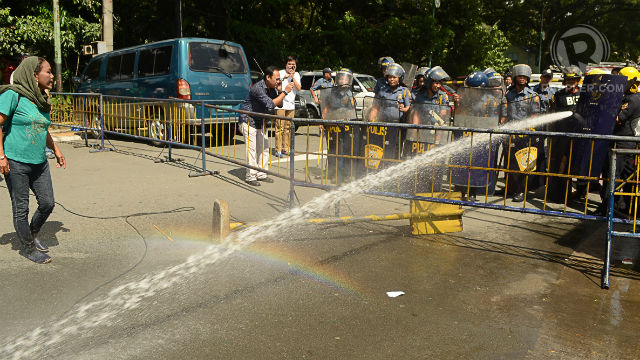 BRUTE FORCE. Policemen use water cannons to keep the protesters from entering the Quezon City hall. Photo by Mark Demayo.