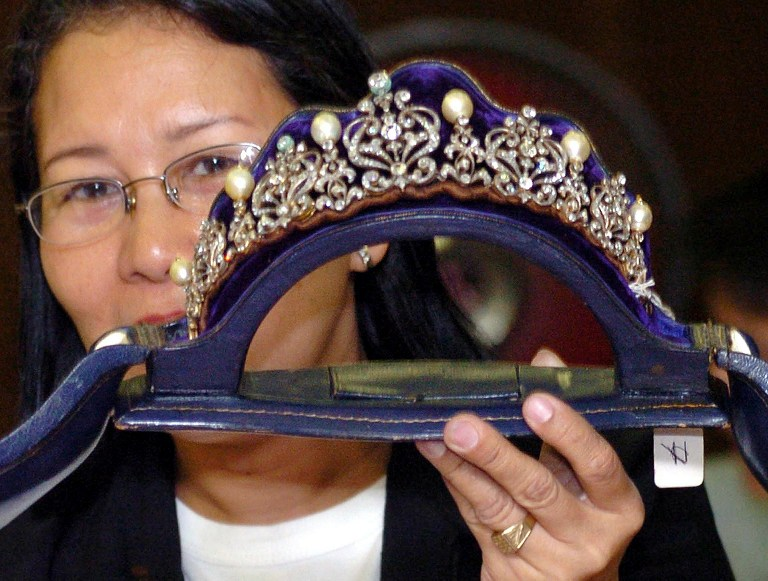 This file photo taken on September 15, 2012 shows a Presidential Commission on Good Goverment (PCGG) official showing at the Central bank headquarter in Manila, a tiara inlaid with diamonds and South Sea pearls from a collection seized by the government from former first lady Imelda Marcos in the late 1980s. AFP PHOTO / FILES / JOEL NITO