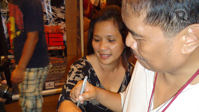 'SUPERCROOKS' INKER GERRY ALANGUILAN seems to be signing a comic book fan's arm u2014 yes, arm. Photo by Jerald Uy