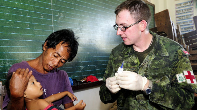 EXPERT CARE. A Canadian medic checks on a child in an evacuation center outside of Roxas City, Capiz. Photo from the Canadian Embassy in Manila.