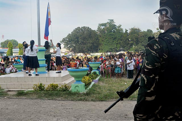 FLAG-RAISING. A soldier looks over a group of students and teachers raising the Philippine flag during the reopening of classes in Sta. Maria Central School. Photo by LeAnne Jazul/Rappler
