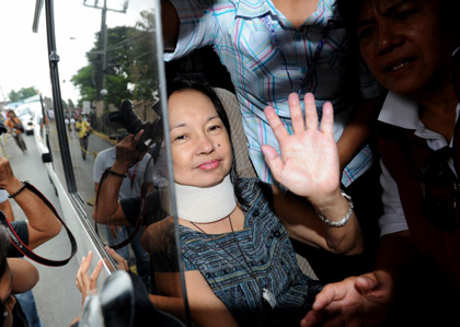 TEMPORARY RELEASE? Arroyo waves at supporters upon arriving home in Katipunan, Quezon City. AFP Photo.