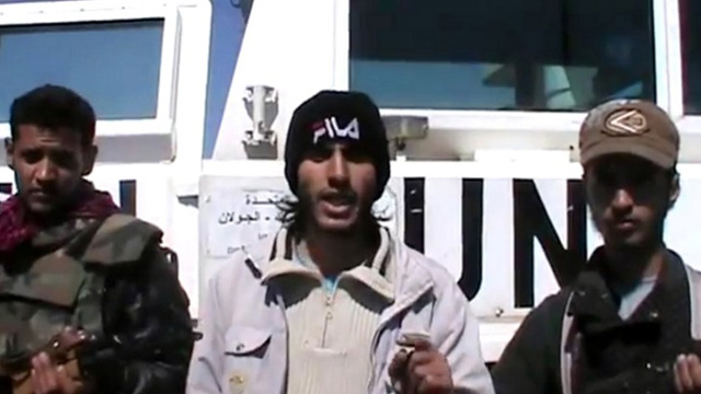 SYRIAN KIDNAPPERS. Screen grab taken from a video uploaded on YouTube on March 6, 2013, allegedly shows armed fighters standing in front of a United Nations Disengagement Force (UNDOF) vehicle in the Golan Heights between Syria and Israel. AFP PHOTO/YOUTUBE