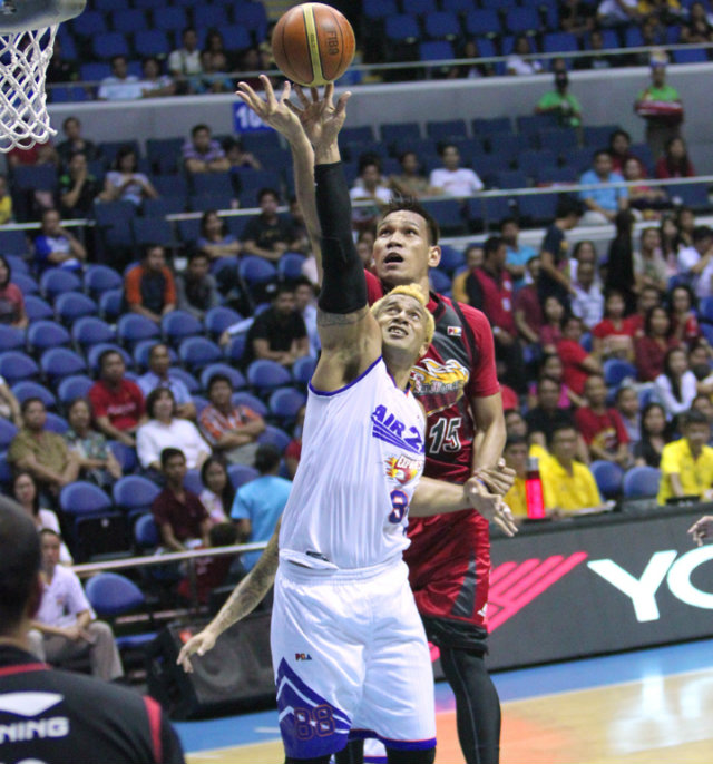 AGE AIN'T NOTHING BUT A NUMBER. Air21's ageless center Asi Taulava puts up a shot as San Miguel Beer's June Mar Fajardo looks on. Photo by Nuki Sabio/PBA Images