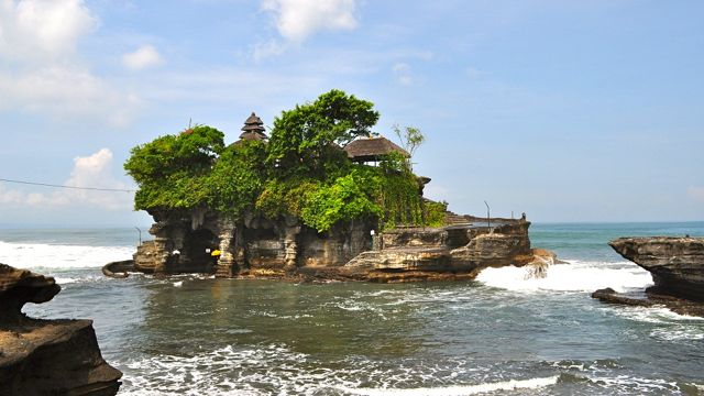 TANAH LOT, WHETHER AT high tide with the pounding surf or at low tide with a colorful sunset, is breathtaking