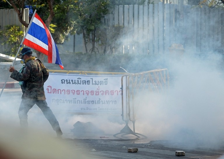 GASSED. A Thai anti government protester holds a national flag during a rally at a stadium to register party-list candidates in Bangkok on December 26, 2013. AFP / Pornchai Kittiwongsakul