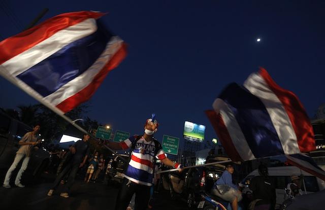 WAVING THE FLAG. A Thai anti-government protester waves national flags during a mass rally blocking a main road in Bangkok, Thailand, 12 January 2014. Narong Sangnak/EPA