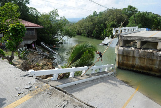 BROKEN CROSSING. Using ropes and a bamboo pole, a resident crosses a bridge that was destroyed during an earthquake in the town of Loon in Bohol. Photo by AFP/Jay Directo
