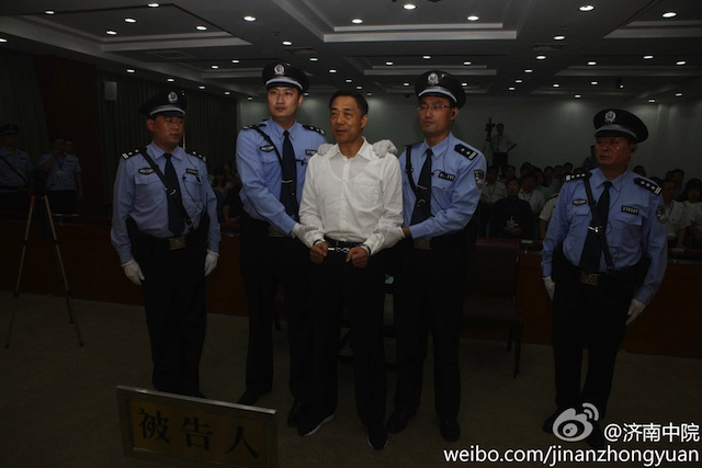 GUILTY. Bo Xilai (center) stands in between police officers while the verdict on his case is being read, inside the Jinan People's Intermediate Court September 22, 2013. Photo courtesy Jinan People's Intermediate Court, via Sina Weibo