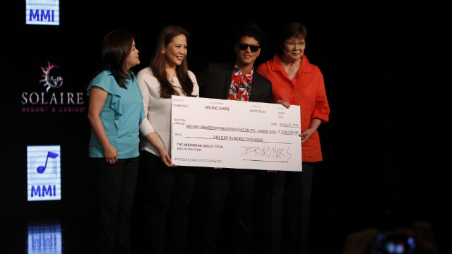 DONATION. Bruno Mars hands a check of $100,000 to ABS-CBN executives to be used in helping kids affected by Typhoon Yolanda