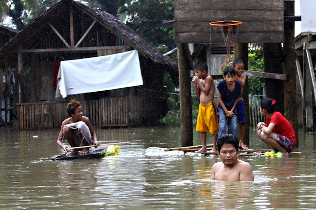 FLOODED. Residents gather next to a flooded basketball court at a village in Butuan City on January 17, 2014, as floods inundated villages and towns after heavy rains. Erwin Mascarinas/AFP