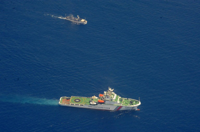 'GREAT EQUALIZER.' A Chinese coast guard ship (bottom) and a Philippine supply boat engage in a standoff on March 29, 2014. Both the Philippines and China cite international law in claiming the West Philippine Sea. Photo by Jay Directo/AFP