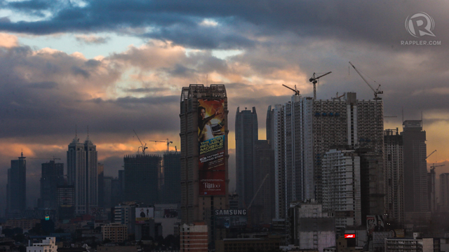 BOOM. Construction workers harnessed to steel bars at a high-rise building construction site in Manila. Photo by AFP
