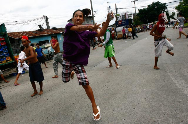 DEFENDING THEIR HOMES. Informal settlers throw broken glass at policemen who were trying to demolish their homes in Agham Road, Quezon City. Photo by Ed Alba.