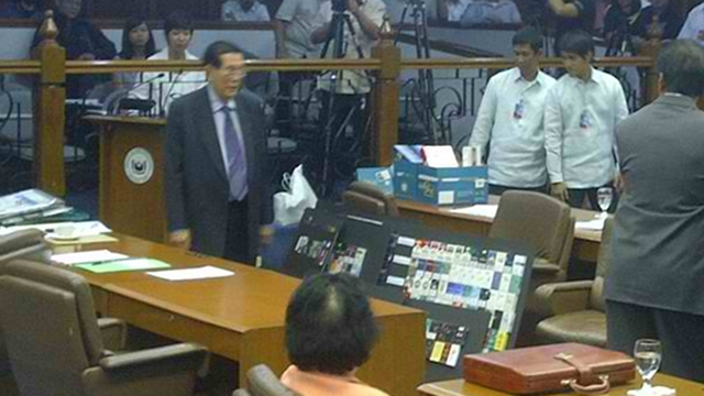 VISUAL AIDS. Senate President Juan Ponce Enrile holds up an illustration board with packs of cigarettes he said were smuggled from abroad. He says the sin tax bill favors foreign manufacturers over local ones because it will worsen smuggling. Photo courtesy of Judee Aguilar/ twitter.com/orangedenims