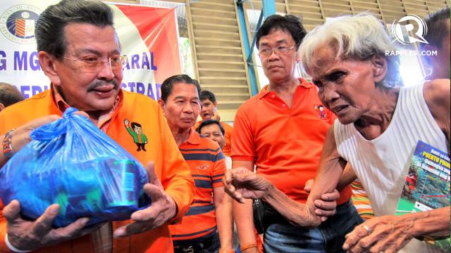 BIRTHDAY RITUAL. Former President Joseph Estrada handed donations from former high school classmates to Tondo residents. Photo by Arcel Cometa