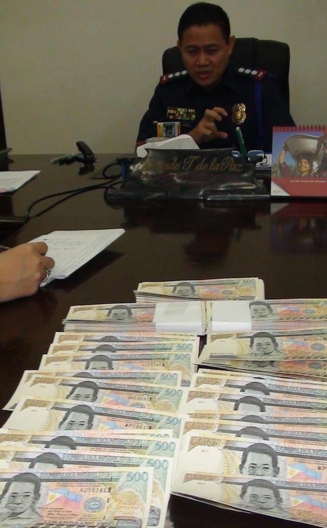 FAKE MONEY. Senior Supt. Ricardo de la Paz, Negros Occidental police officer-in-charge, presents the P150,000 worth of fake P500 bills. Rappler/Gilbert Bayoran