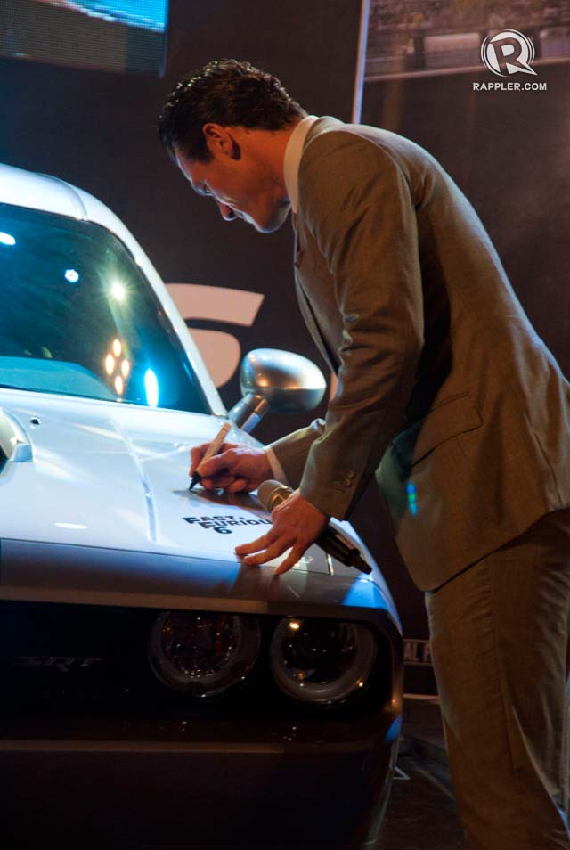 AUTOGRAPHED SPORTSCAR. Luke Evans signs the Chrysler Dodge to be auctioned off for charity