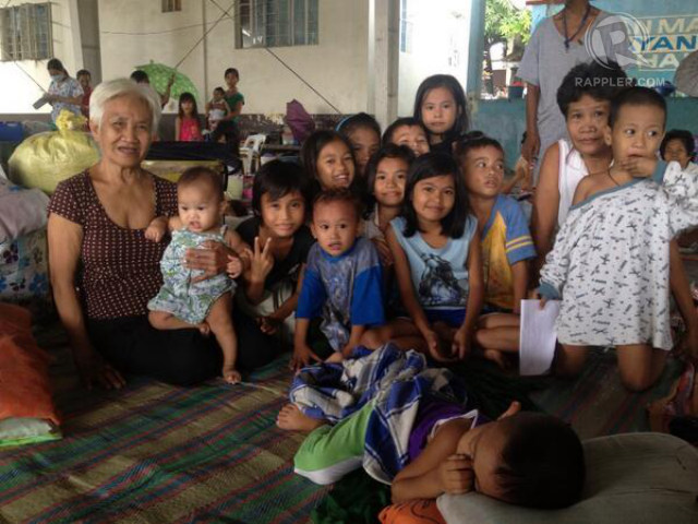 LAUGHING BUT SAD. Rosenda Infante, who has 40 grandchildren (not all in photo), wants a home safer from flooding. Photo by Paterno Esmaquel II