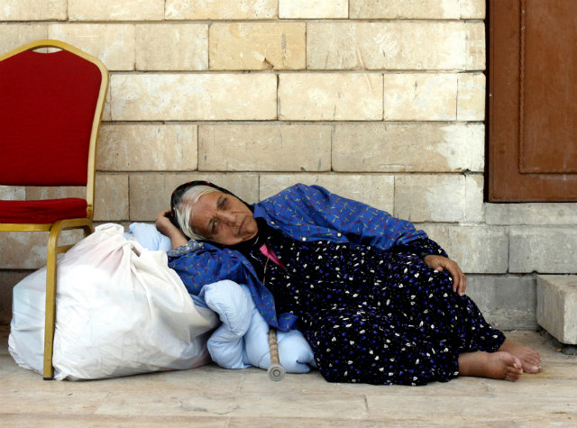 FEAR OF PERSECUTION. An Iraqi Christian woman forced to flee her home shelters in the St Joseph Church in Erbil, northern Iraq, on August 9, 2014. Photo by Mohammed Jalil/EPA