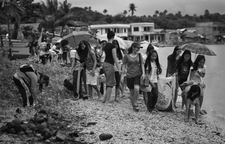 PICKING UP TRASH. Volunteers and kids from Puerto Galera scour the beach to pick trash. Photo by Jadd Padilla