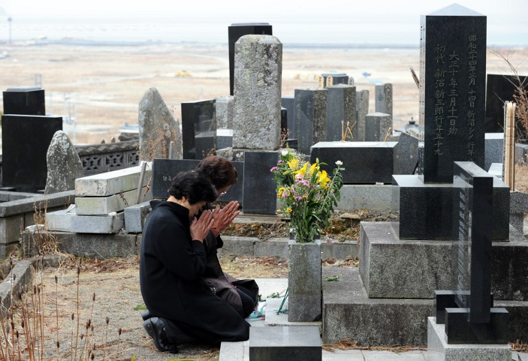 TWO YEARS. Sumiko Yoshida (R, w/glasses) and her sister Katsue Nagano (L) pray at the tomb during the prayers for five of their family members who were killed in the March 11, 2011 tsunami in Rikuzentakata city one day before the second anniversary of the March 11 earthquake and tsunami disasters, in Rikuzentakata on March 10, 2013. AFP PHOTO / TOSHIFUMI KITAMURA