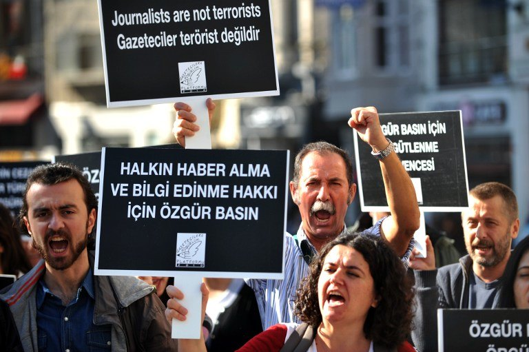 PROTEST. A journalist raises his fist and chants slogans as another holds a sign reading u0022The public has the right to real newsu0022 during a protest calling for media rights in Turkey on November 5, 2013, on the Istiklal Avenue in Istanbul. AFP/Ozan Kose