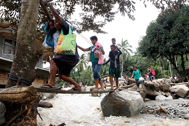 INTENSE FLOODING. Residents walk over a makeshift bridge passing flood waters caused by a landslide after heavy rains in Marayag Village, Lupon town, Davao Oriental. Photo by EPA/Ritchie Tiongco
