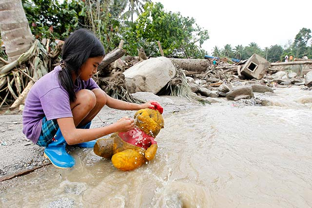 OUT FOR A BATH. Weldel Sametos, 10, scrubs her stuff toy in flood waters after heavy rains in Marayag Village, Lupon, Davao Oriental. Photo by EPA/Ritchie Tiongco