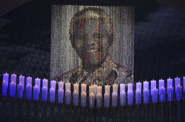 FINAL FAREWELL. Candles are lit under a portrait of Neslon Mandela before the funeral ceremony of South African former president Nelson Mandela in Qunu on December 15, 2013.  AFP / Pool / Odd Andersen