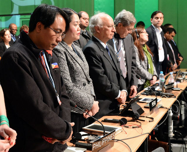 A MOMENT OF SILENCE. Naderev Sano and other delegates pay standing tribute to victims of Typhoon Haiyan during the UN Climate Change Conference COP 19 on November 11, 2013  AFP PHOTO/JANEK SKARZYNSKI