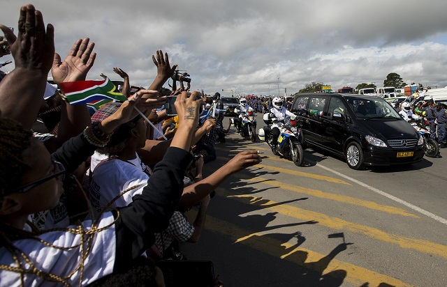 HOME. Thousands of people lining the streets cheer as the hearse carrying the body of Nelson Mandela drives from Mthatha to Qunu, South Africa, December 14. Photo by Ian Langsdon/EPA