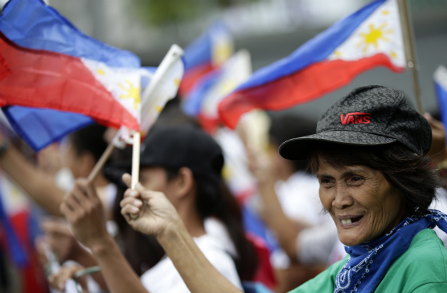 BOTH CLAIMANT-COUNTRIES. Filipinos wave Philippine flags as they join Vietnamese nationals in a commemoration of the Vietnam-China border war in 1979, in front of the Chinese consulate in Makati on Feb 17, 2014. Protesters aim to support Manila in an ongoing stand-off with China. File photo by Dennis Sabangan/EPA