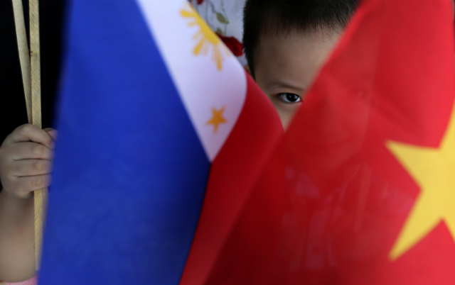 'ON SAME SIDE.' A Vietnamese child peers from Vietnam and Philippines flags while waiting for the arrival of Vietnam Prime Minister Nguyen Tan Dung at Villamor Airbase in Pasay, south of Manila, Philippines on May 21, 2014. File photo by Dennis Sabangan/EPA