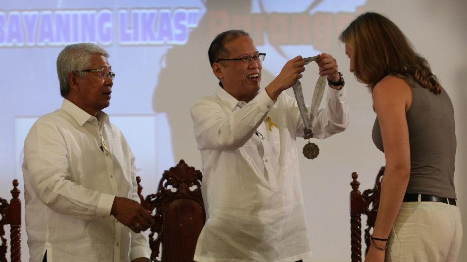 President Aquino and Defense Secretary Voltaire Gazmin present the Bakas ng Parangal ng Kagitingan bronze medallion to Malapascua American volunteer technical diver Shelagh Cooley. Cooley was among three volunteer technical divers from Cebu who helped in the search operations for Robredo. Photo by Malacau00f1ang Photo Bureau