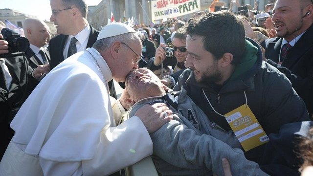 CHARISMATIC PONTIFF. Before his homily about care for creation, Pope Francis stops to kiss a sick man during his inaugural procession. Photo from Vatican Radio's Facebook page