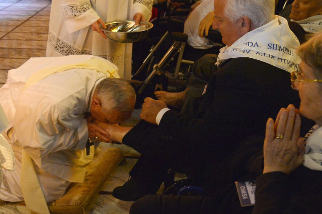 SYMBOL OF SERVICE. Pope Francis (L) kisses the foot of a man as he performs the traditional 'Washing of the Feet' during a visit at a center for disabled people as part of Holy Week on April 17, 2014 in Rome. Photo by Alberto Pizzoli/AFP